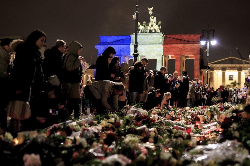 Бранденбургската врата в Берлин свети в синьо, бяло и червено, докато хора поднасят цветя в близост до френското посолство