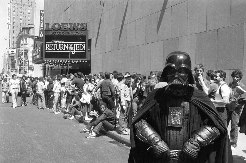 """Почитател на Дарт Вейдър позира пред опашката на Таймс Скуеър, Ню Йорк. Датата е 23 май 1983 година, а събитието се нарича """"Завръщането на джедаите"""""""